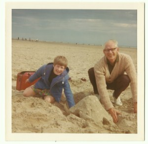 Dad and me building sandcastles on holiday. Red bag in background!